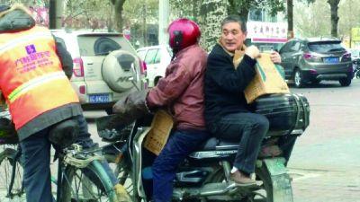 太危险!男子抱箱子反坐摩托车