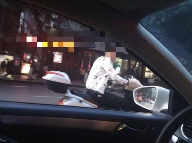 心大!小伙单手骑摩托车玩微信